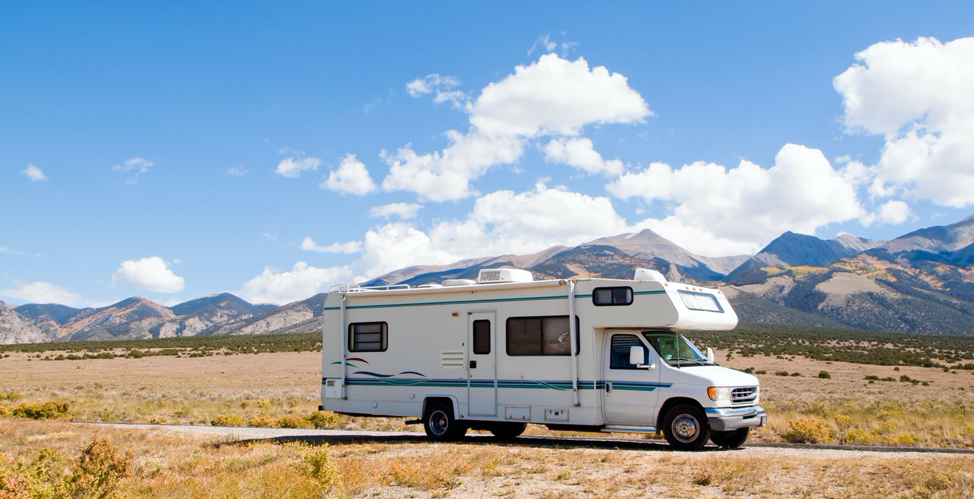 A class C motorhome driving with mountains in the background.
