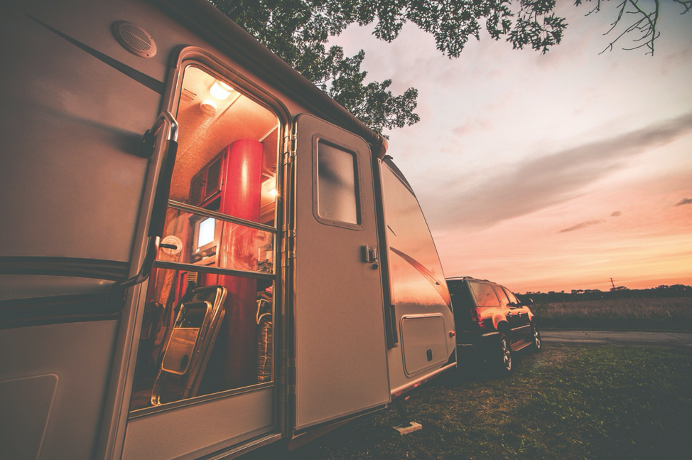 The exterior of a travel trailer with the sunset in the background.