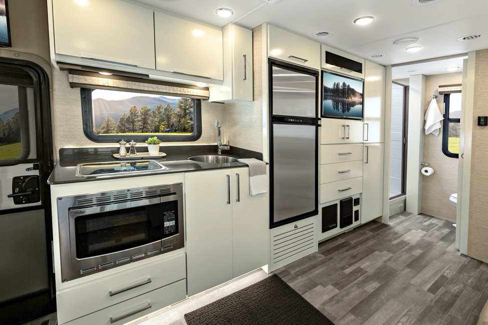 The kitchen inside the new 2020 Tiffin Wayfarer with linen cabinets and reston ivory wall coverings.