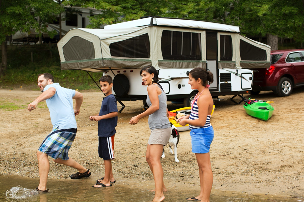A family playing in a lake with their pop-up camper behind them.