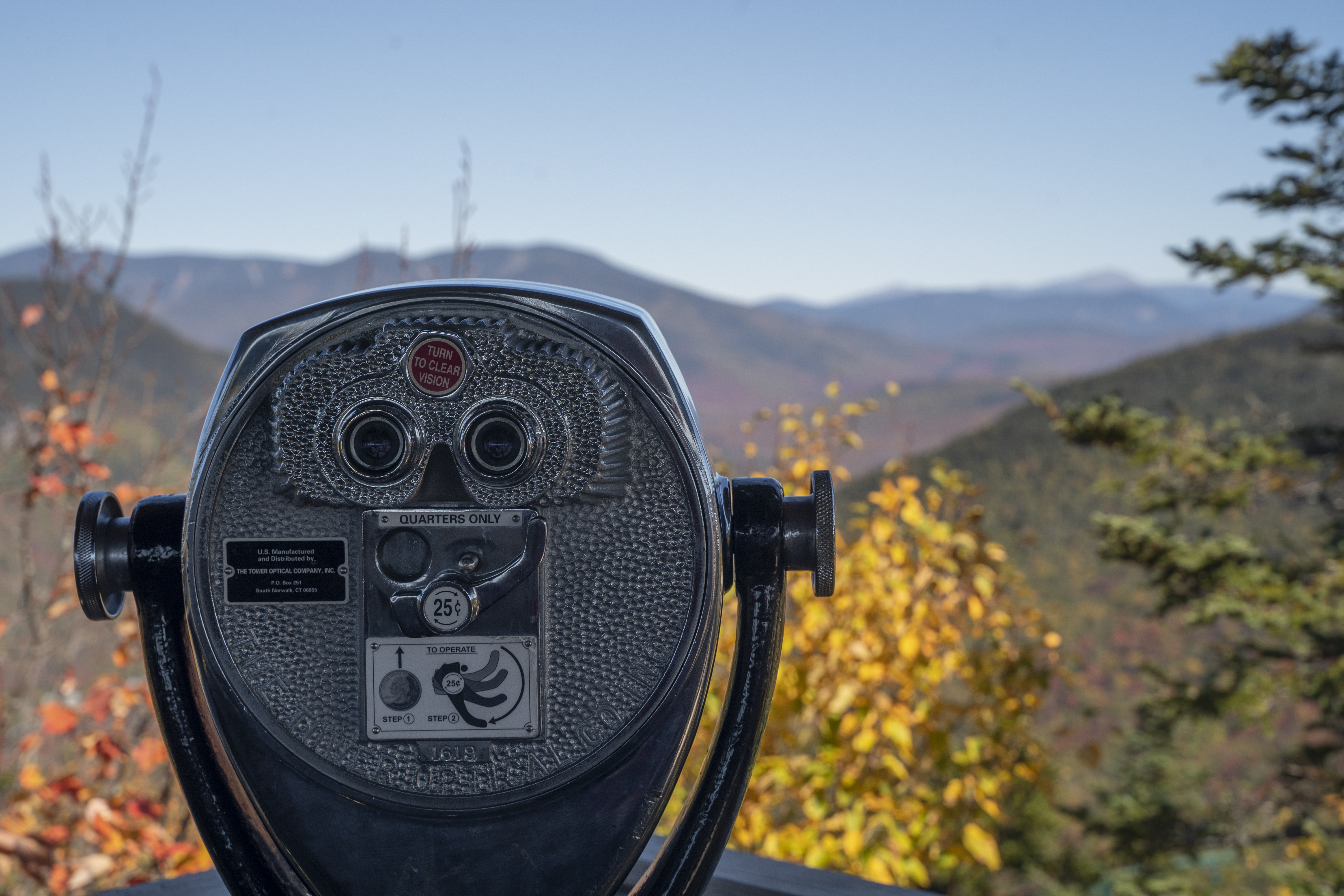 A photo of binoculars overlooking mountains with fall leaves.