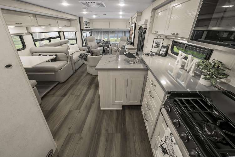 The interior of the 2020 Winnebago Forza in the mineral contemporary option, featuring neutral tones and luxury wood plank flooring.