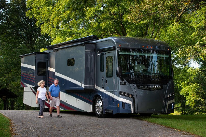 The 2018 Winnebago Forza with a couple walking in front of it as it is parked.