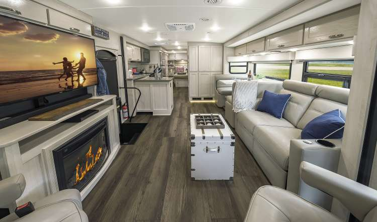 The interior of the new 2020 Winnebago Forza featuring a fireplace and LED Television.