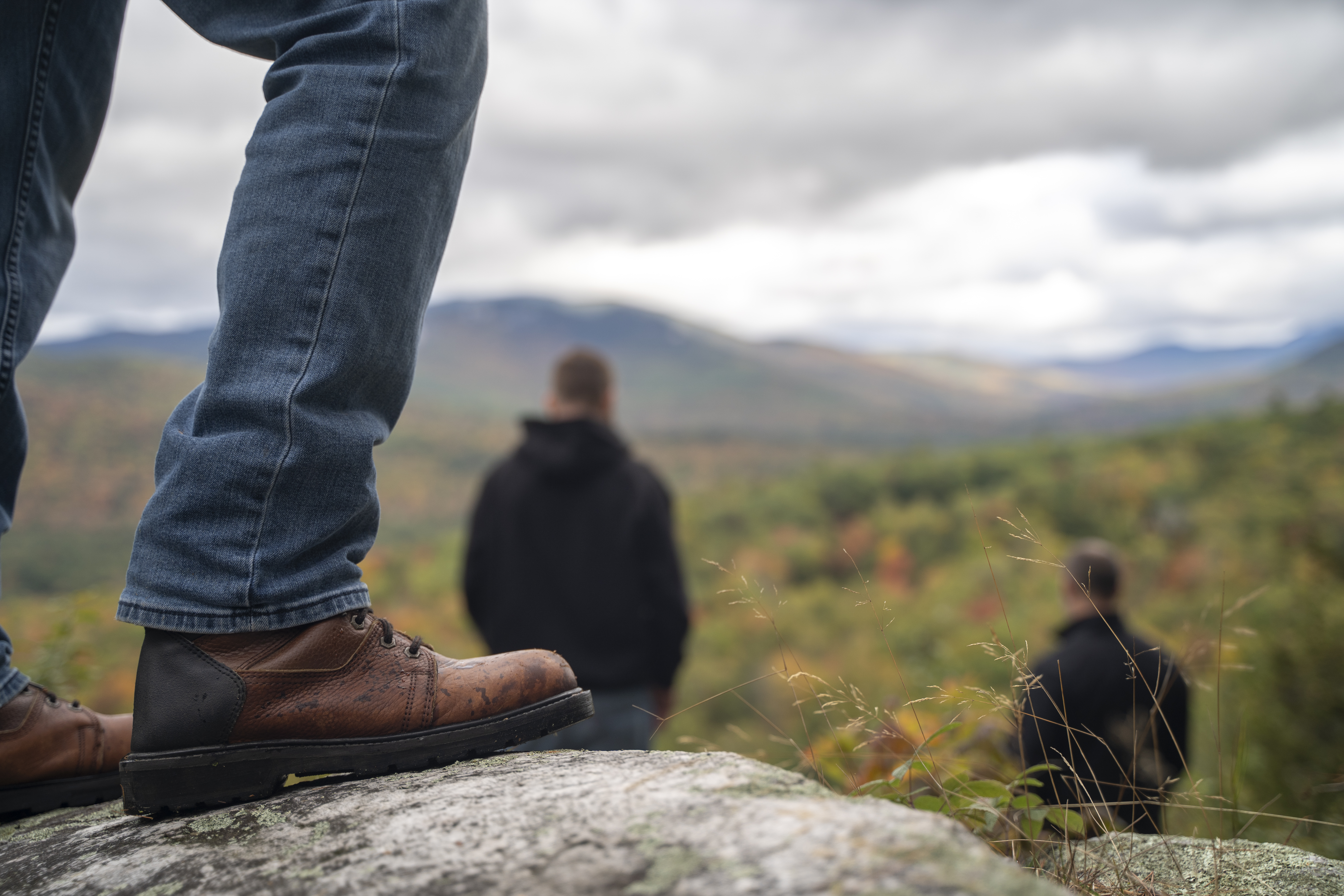 A person standing on the top of a mountain overlooking the fall colors.