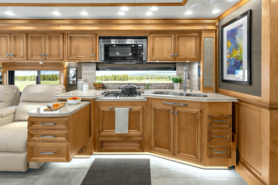 The interior of the 2020 Tiffin Phaeton's kitchen in amber glazed and trend beige.
