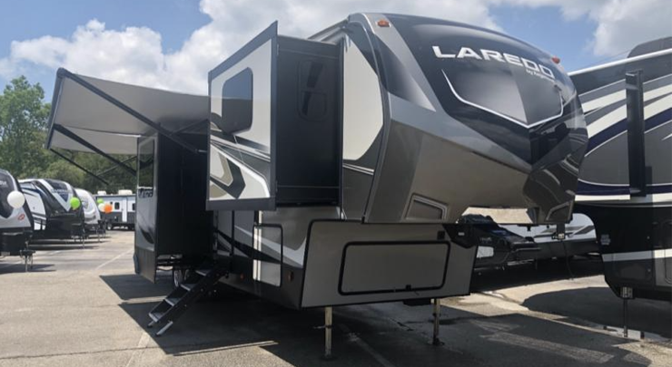 The exterior of the 2020 Keystone Laredo 353FL Fifth Wheel featuring four slideouts and a power adjustable awning.