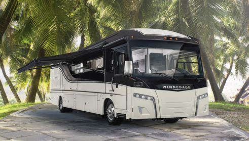 A class A Winnebago motorhome with tropical palm trees behind.