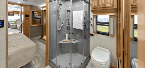 : A Class A Tiffin Phaeton motorhome, featuring a walk-in glass shower and double entry bathroom.