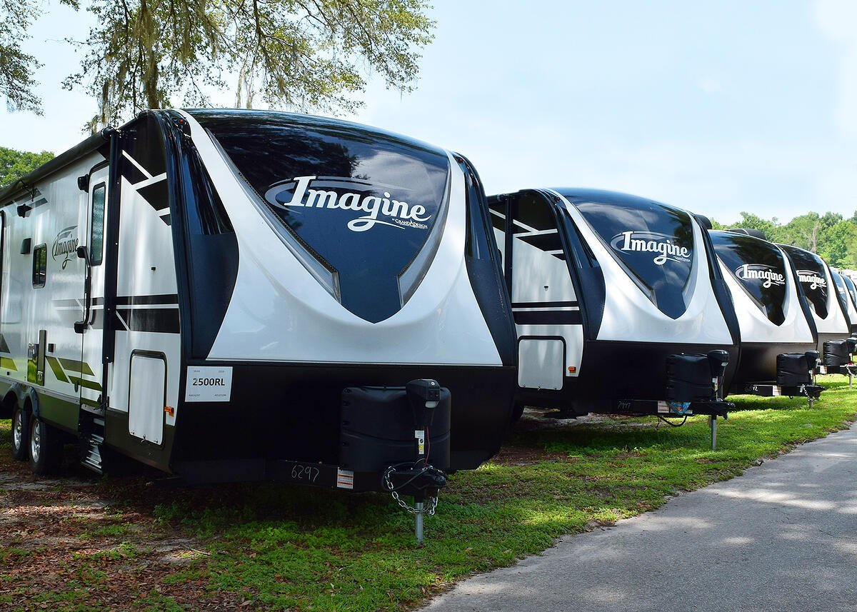 a line up of grand design imagine travel trailers