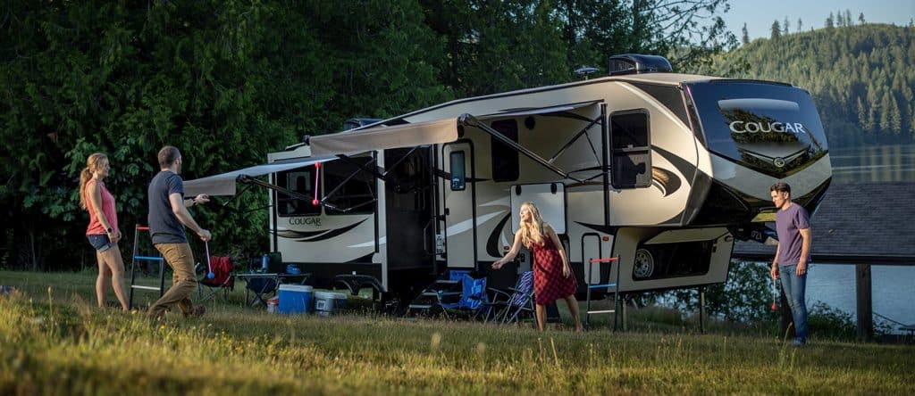 The exterior of a cougar fifth wheel while a family plays outside together